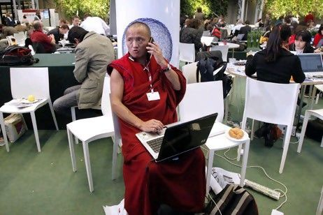 Tibetan monk on call phone and computer